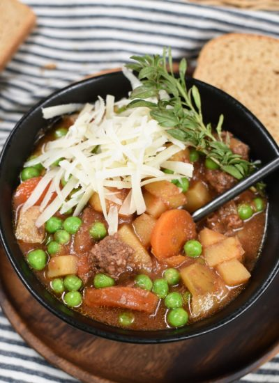 a black bowl with beef stew topped with cheese and herbs