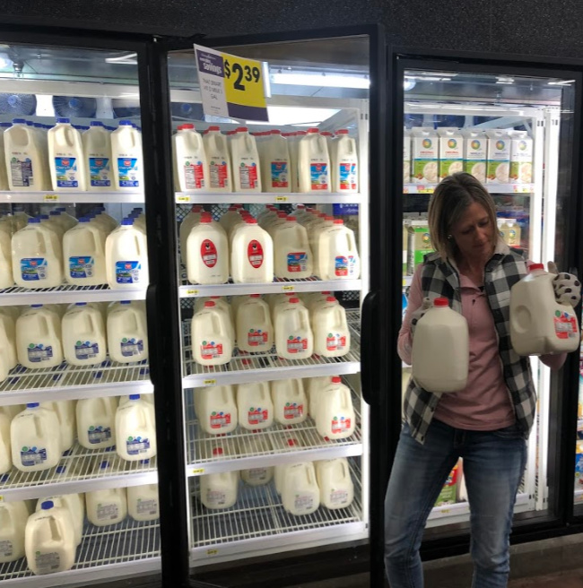 a woman holding two gallons of milk in front of the dairy case at the grocery store
