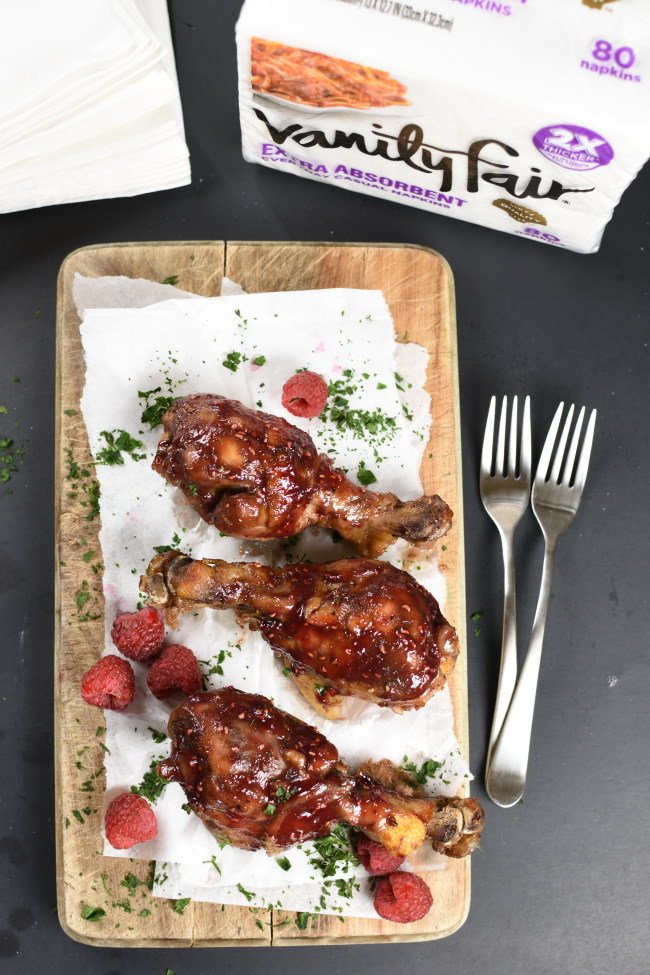 glazed chicken drumsticks on a parchment lined board with raspberries scattered around