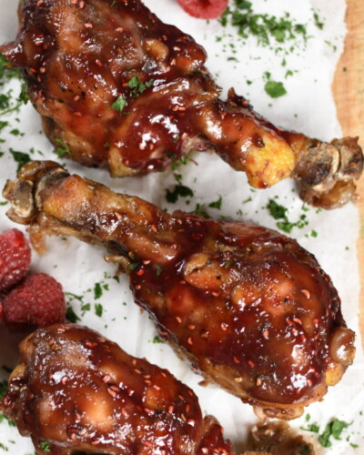 raspberry drumsticks on a white paper lined sheet with raspberries and parsley sprinkled over the top