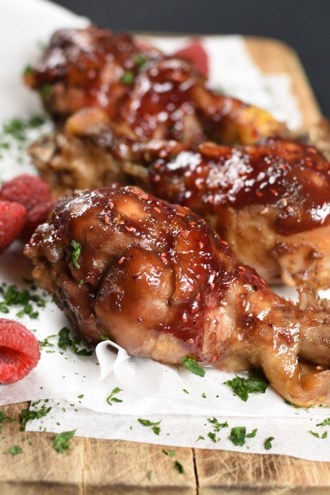 raspberry glazed chicken drumsticks on a white paper