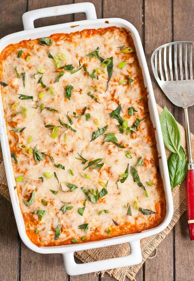 a white baking dish with baked cheesy casserole, sprinkled with fresh basil