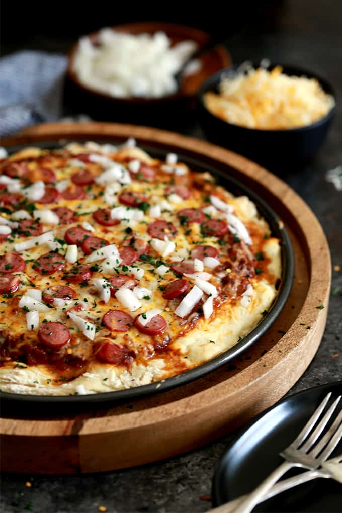 A round pizza pan with baked pizza with sliced hotdogs, cheese, and onions
