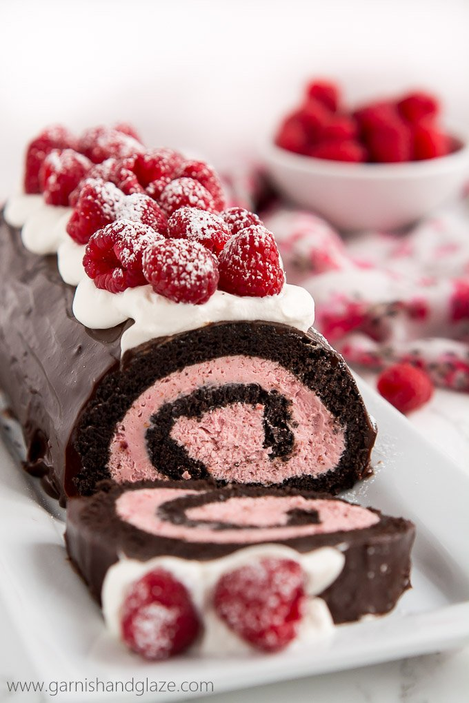 a chocolate cake roll with raspberry cream rolled inside, buttercream and fresh raspberries on top