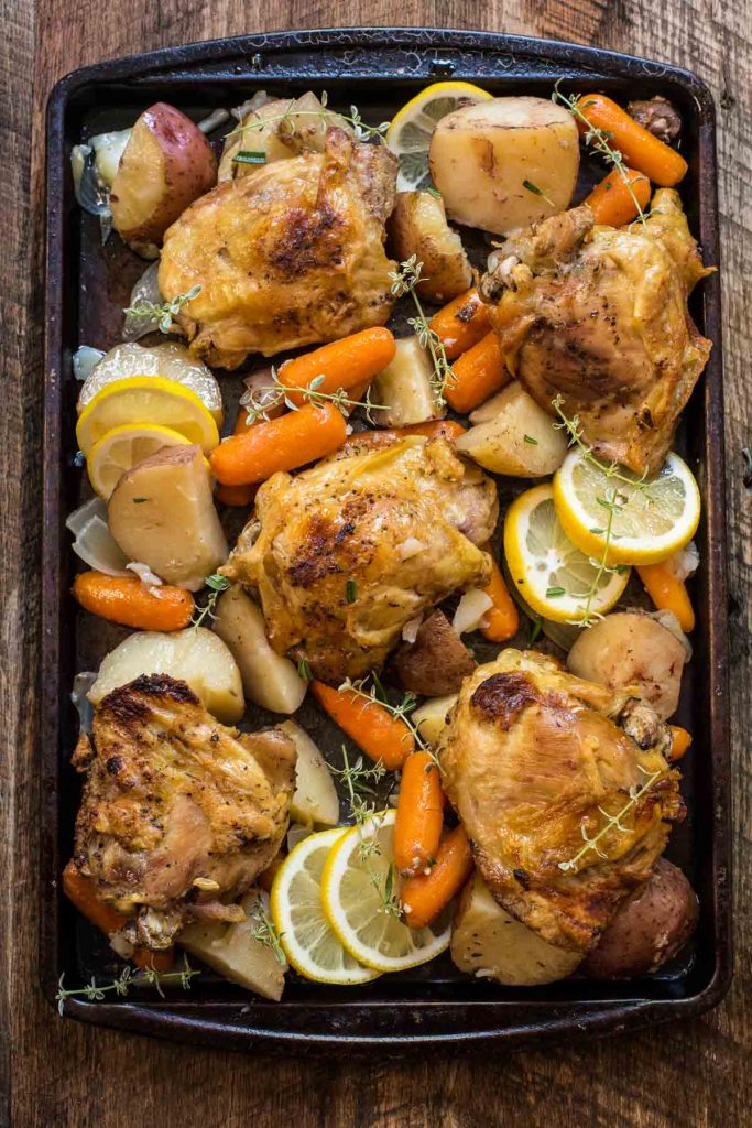 baked chicken and vegetables on a baking sheet with sliced lemons