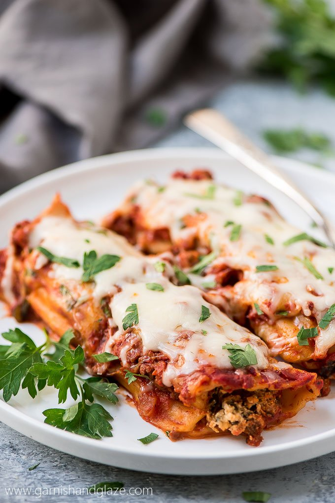 two baked beef manicotti with grated cheese and chopped parsley