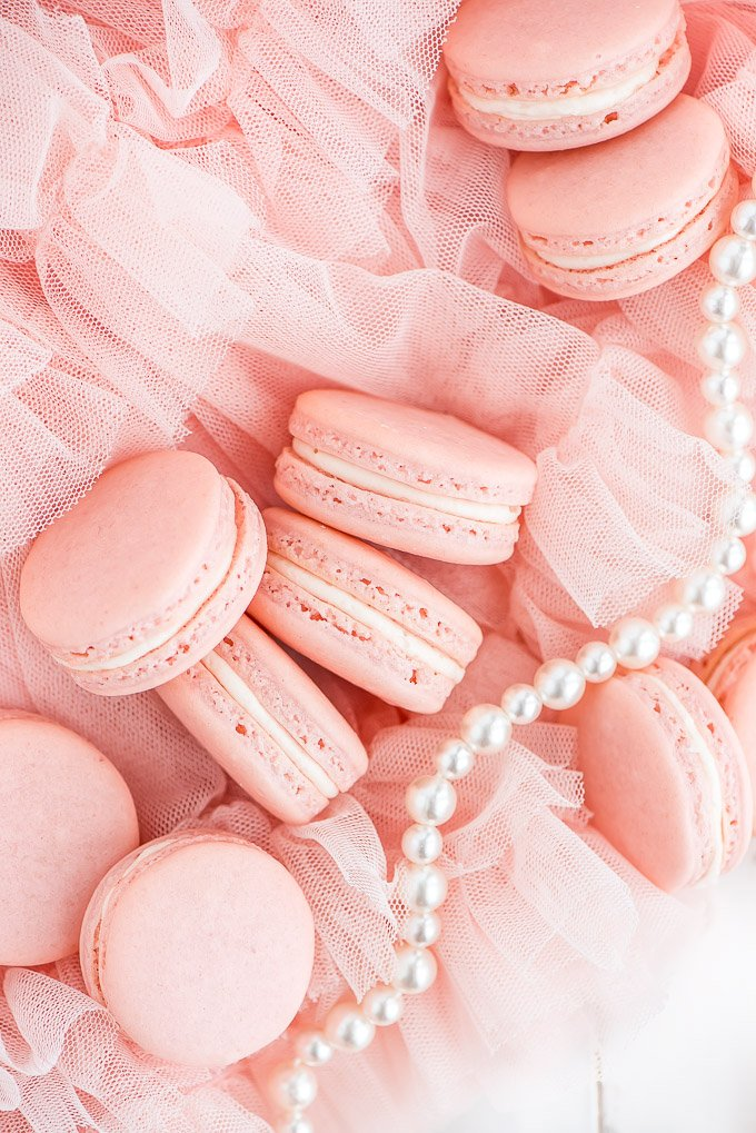 pink macarons with pink icing in the middle on pink netting and pearls