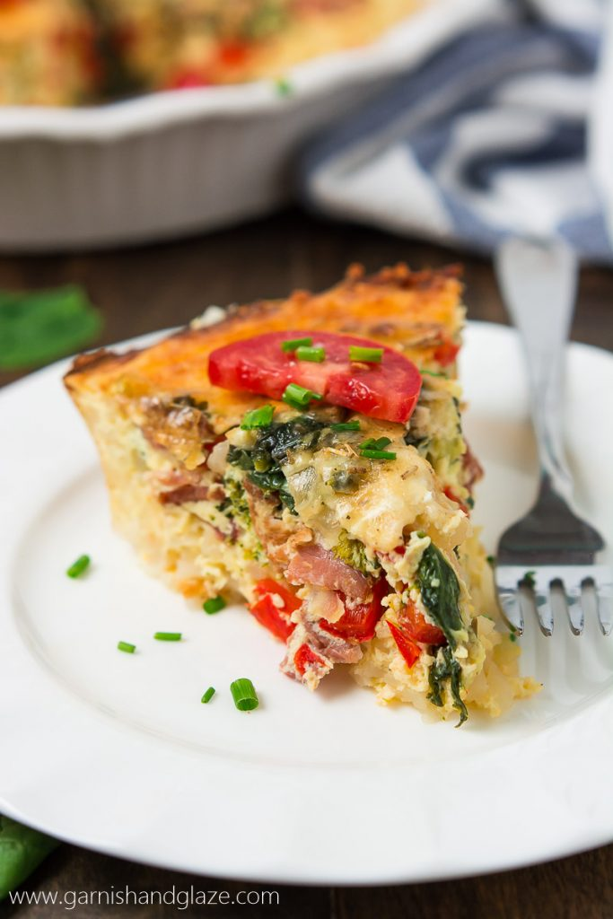 a slice of quiche ona white plate with a sliced tomato on top and minced parsley