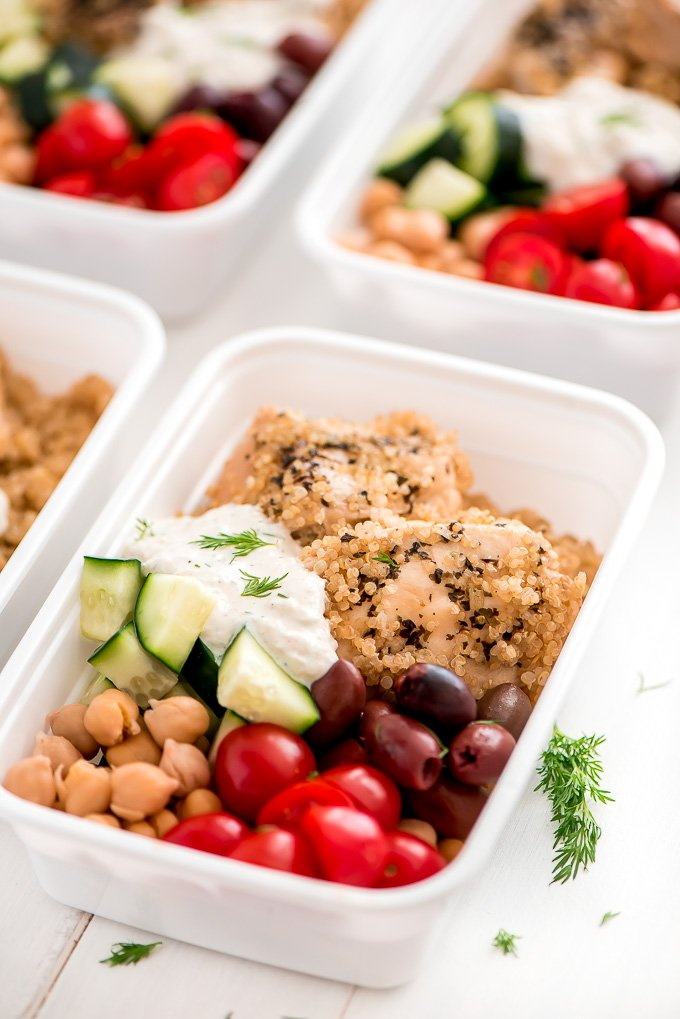 square plastic storage containers with tomatoes, chickpeas, chicken, cucumbers, olives and quinoa