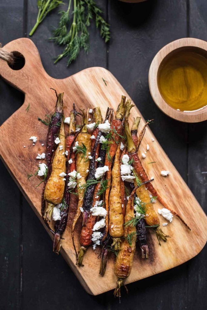 multi colored whole carrots on a wood cutting board sprinkled with feta cheese