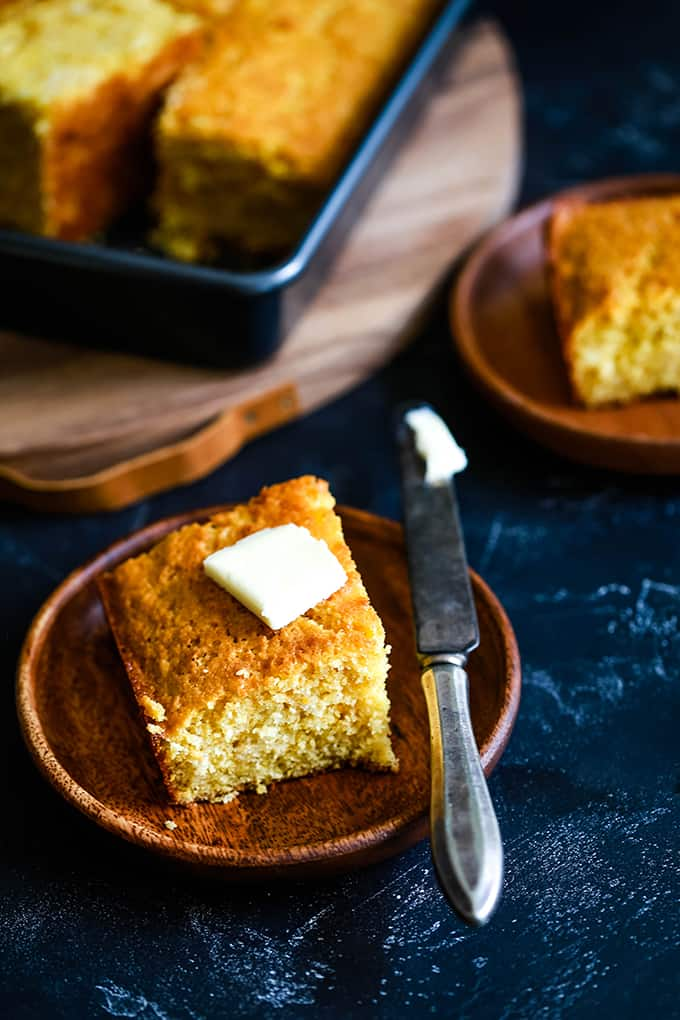 a square of baked cornbread with a pat of butter on top