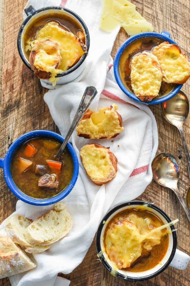 a blue bowl of french onion beef stew with slices of cheese bread