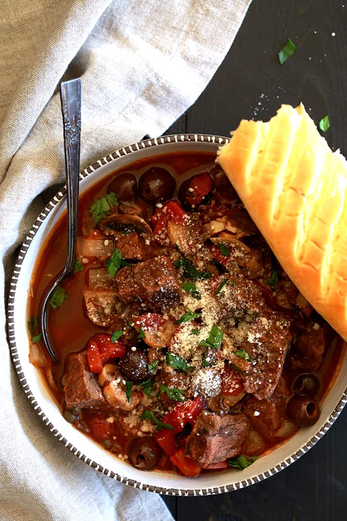 A white bowl of mediterranean beef stew sprinkled with parmesan and chopped parsley