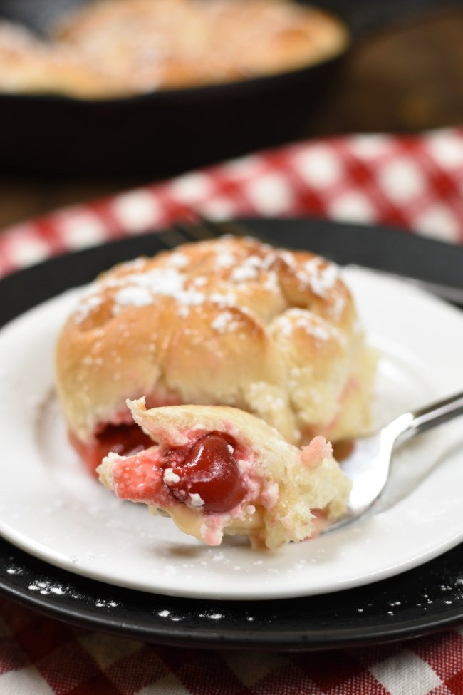 one piece of baked cherry cheesecake monkey bread on a plate with a bite on a fork