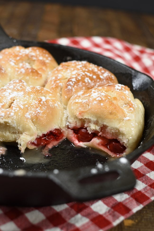 Baked Cherry Cheesecake Monkey bread, dusted with powdered sugar in a cast iron skillet