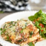 baked ravioli casserole on a plate with green salad