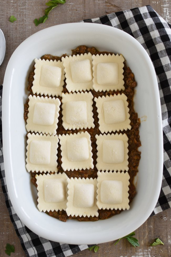 layers of marinara sauce and frozen ravioli in a white baking dish