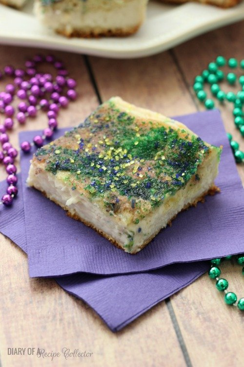 a crescent roll cheesecake square sprinkled with purple and green sugar, on a purple napkin decorated with beads