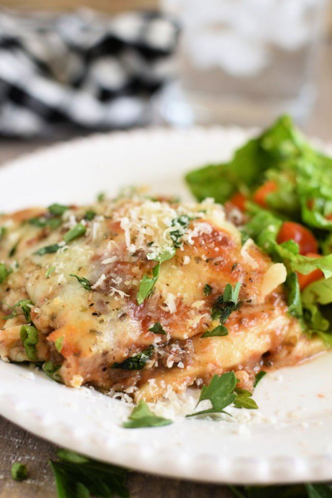 baked ravioli casserole on a white plate served with green salad