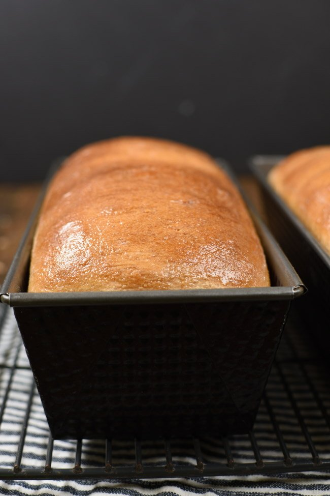 golden brown, baked whole weaht bread in a black loaf pan