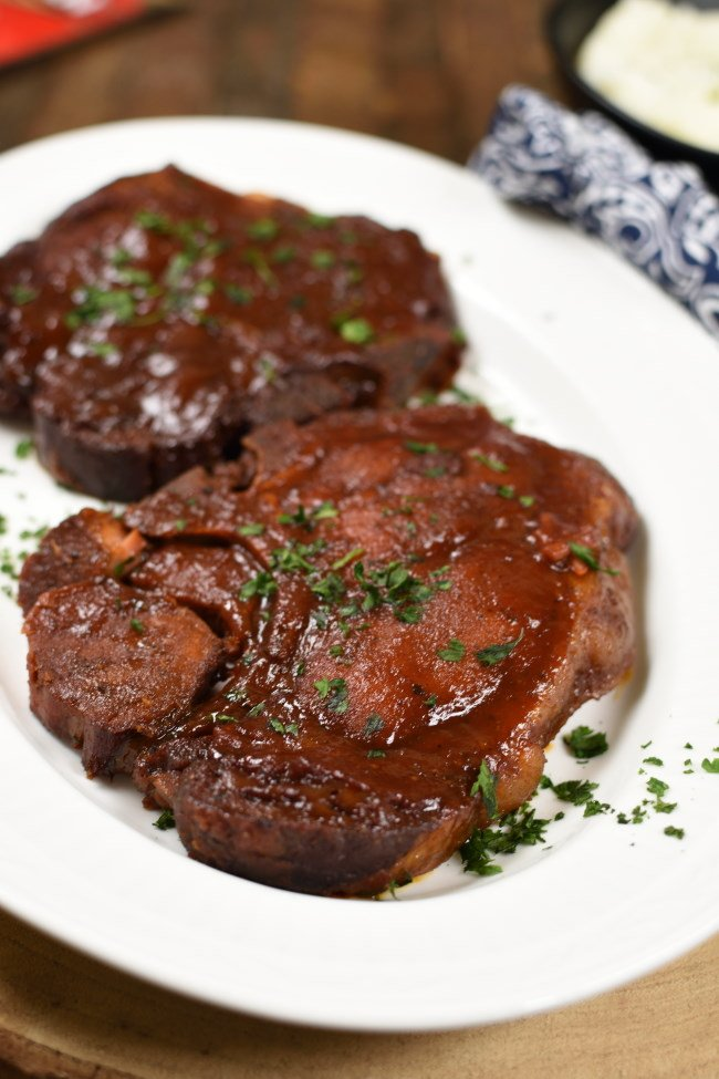 a white platter with two cooked pork chops basted with BBQ sauce and sprinkled with parsley