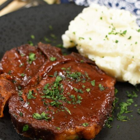 A cooked pork chop basted in BBQ sauce on a black plate with mashed potatoes