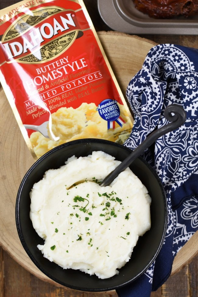 A bowl of mashed potatoes and an package of mashed potatoes with a blue napkin