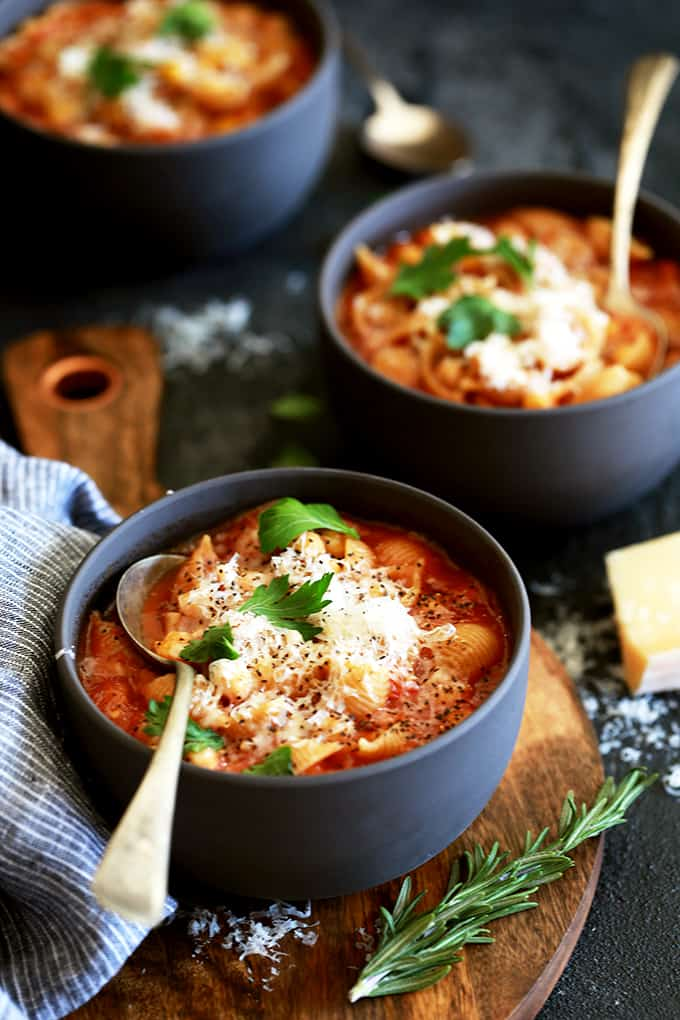 two black bowls filled with red pasta and chickpea soup, garnished with parsley and grated parmesan