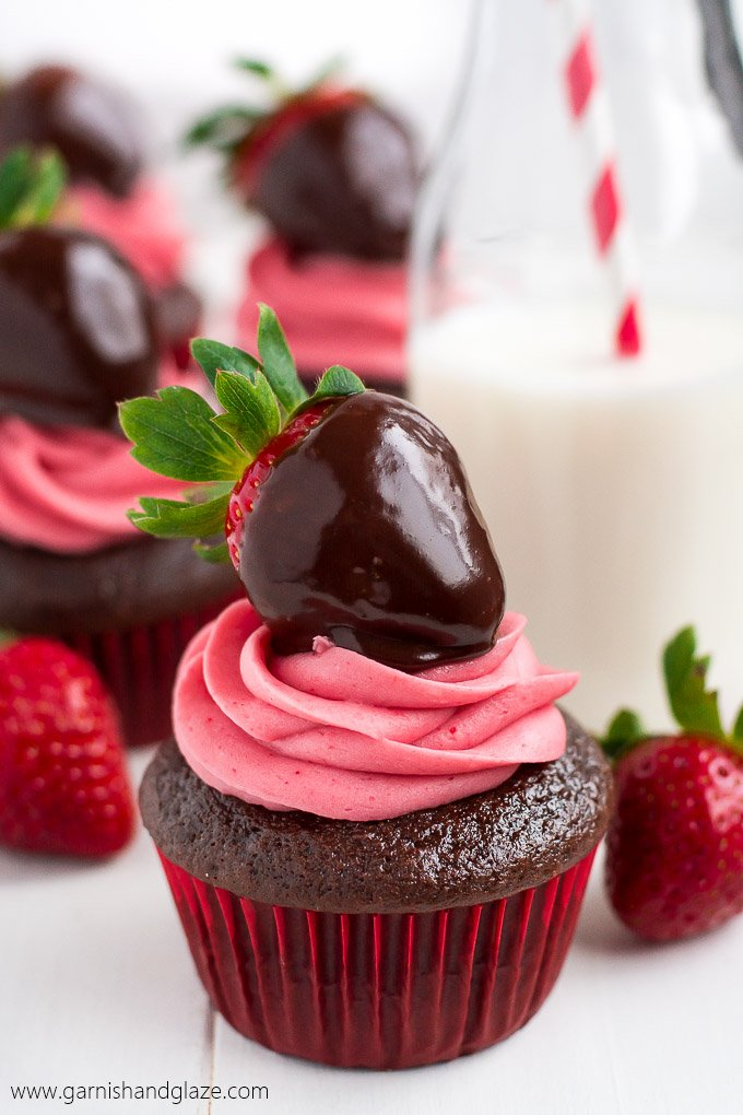 A chocolate cupcake piped with pink icing and topped with a chocolate covered strawberry.