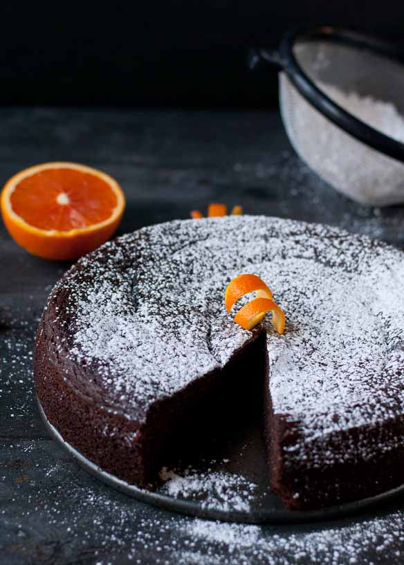 a single layer round chocolate cake dusted with powdered sugar and orange peel