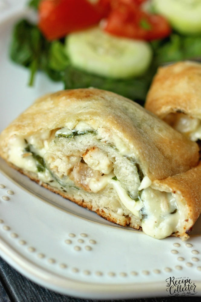 a calzone stuffed with chicken and spinach on a plate with a green salad