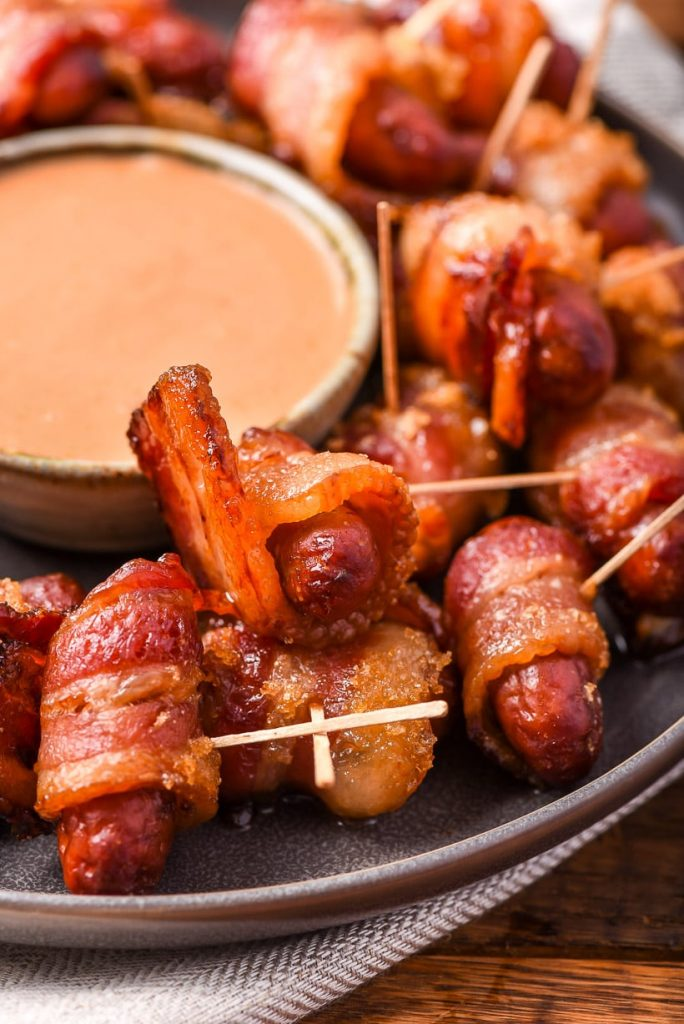 A tray with bacon wrapped smokies with toothpicks, and a dish of pink sauce in the  middle