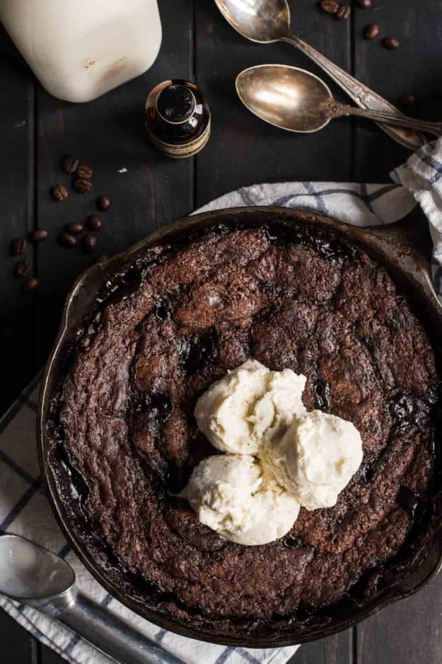 a top view of chocolate cake in a cast iron skillet topped with scoops of icecream