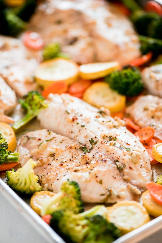 A sheet pan with roasted tilapia and vegetables