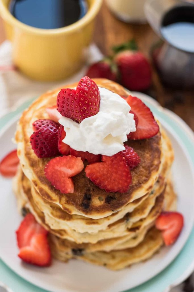 a stack of pancakes topped with heart shaped strawberries and whipped cream