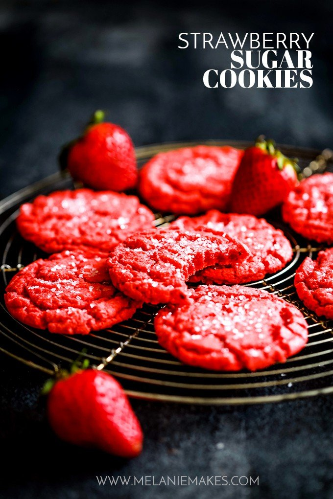 red sugarcookies on a round, black cooking rack with strawberries scattered around