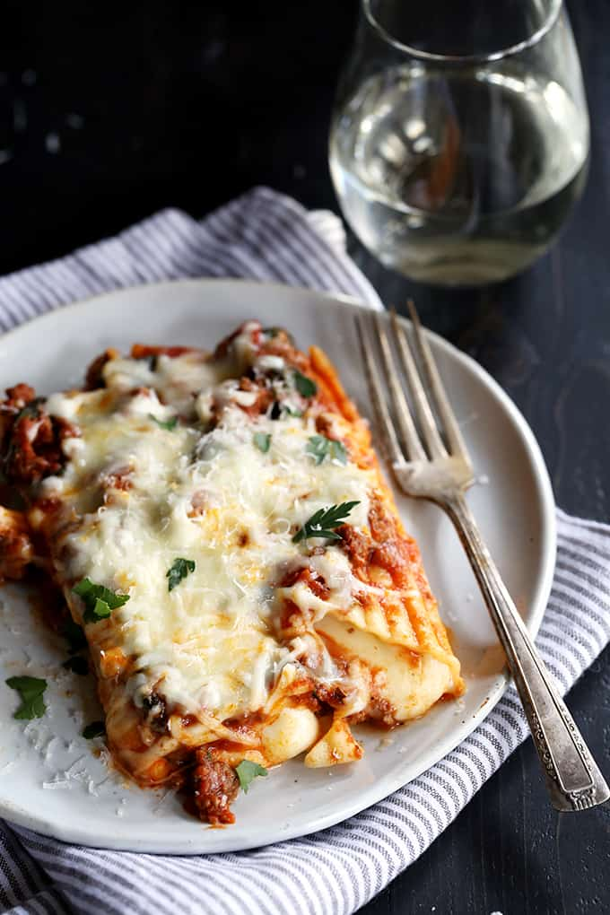 manicotti on a plate with melted mozzarella cheese sprinkled with parsley
