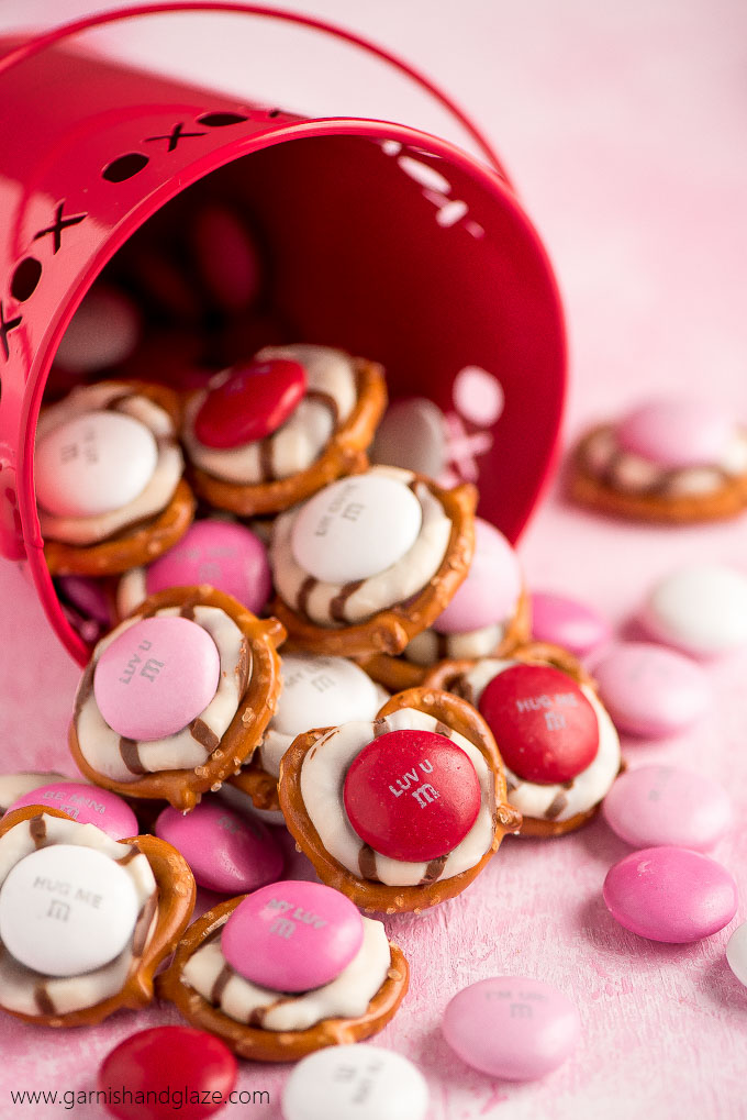 a red pail filled with pretzels topped with a melted striped hug and pink and red candies