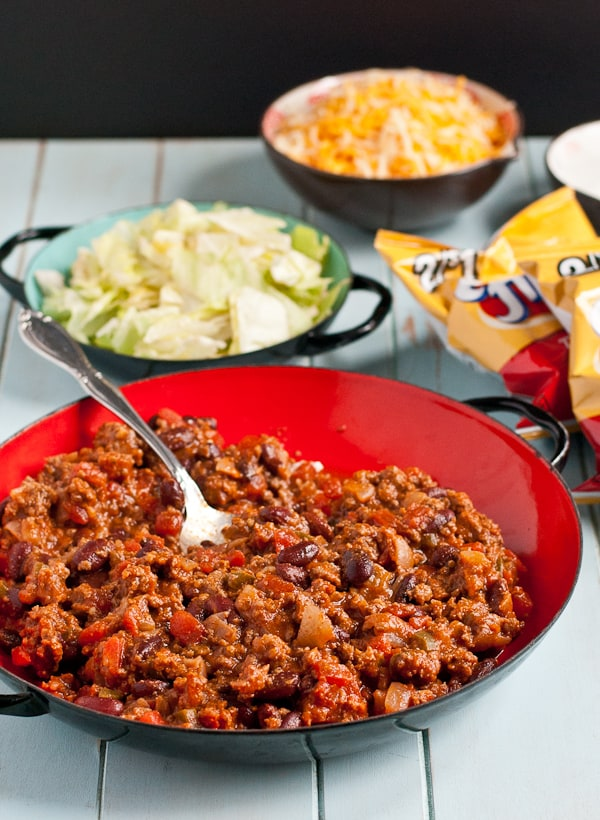 bowls filled with taco meat, sliced lettuce, grated cheese, and a bag of corn chips