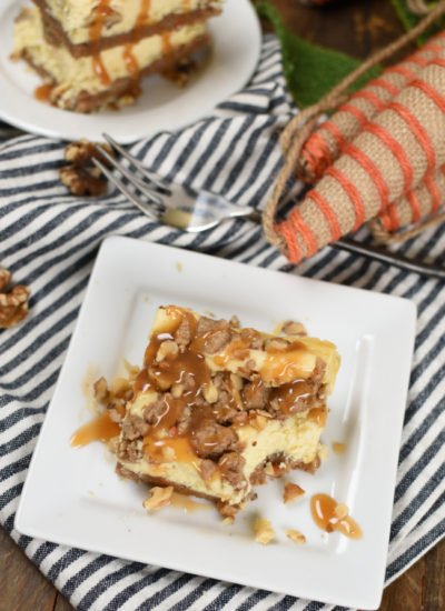 a square of cheesecake on with carrot cake stressel and chopped walnuts