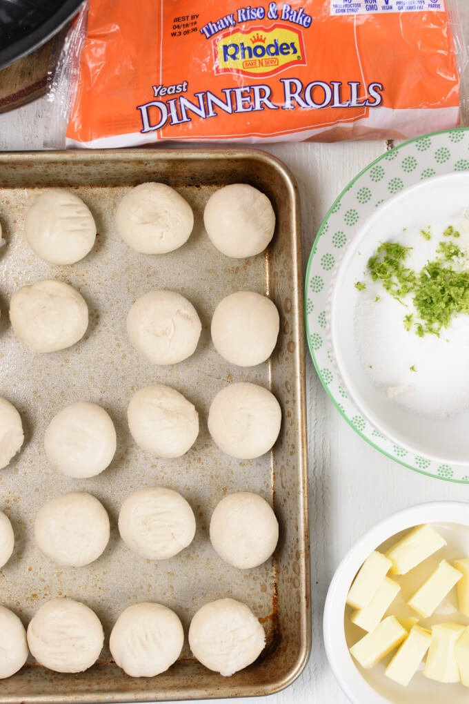 a sheet pan with frozen ball of dough and a bowl with lime zest and sugar, a bowl of sliced butter, and a Rhodes bread bag