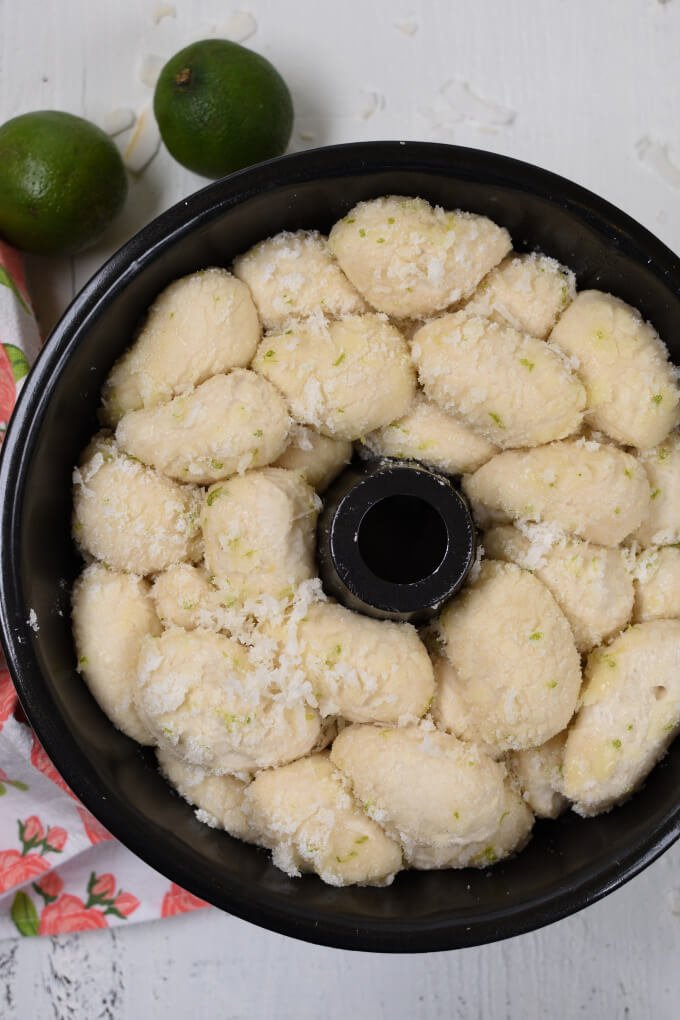 unbaked monkey bread tossed with sugar, coconut, and lime zest in a monkey bread pan