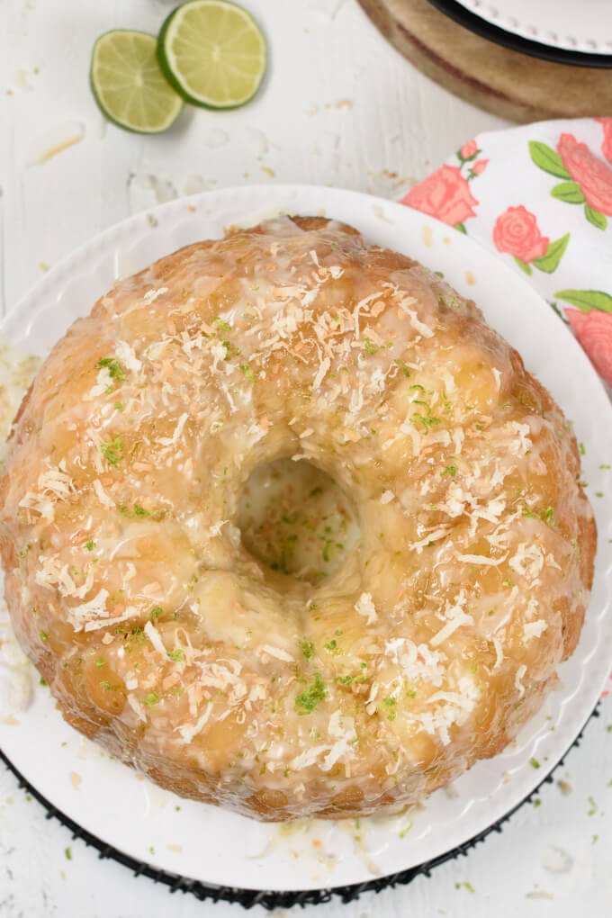 Overhead image of a bundt pan shaped loaf of baked monkey bread on a white plate and sliced limes in the background