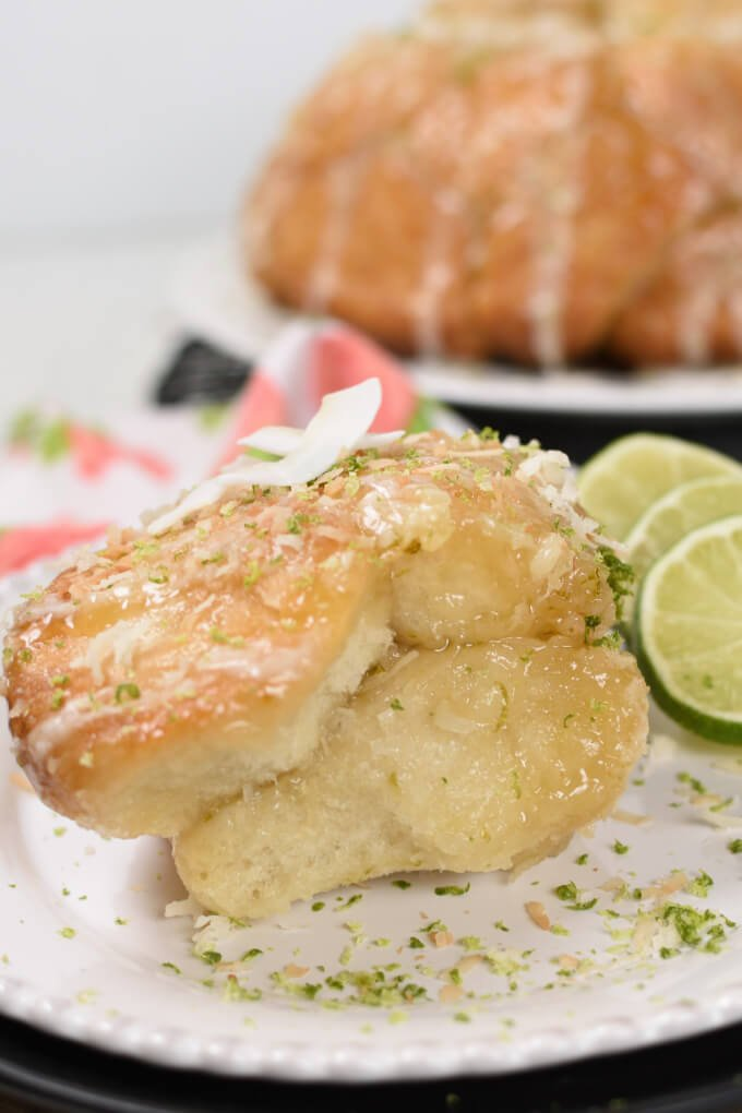 a serving of pull apart bread on a plate sprinkled with lime zest and coconut, garnished with lime slices
