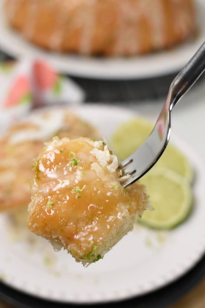 A bite of monkey bread on a fork with a plate of monkey bread and slilces of lime in the background