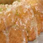 a close up image of baked and glazed monkey bread sprinkled with toasted coconut and lime zest