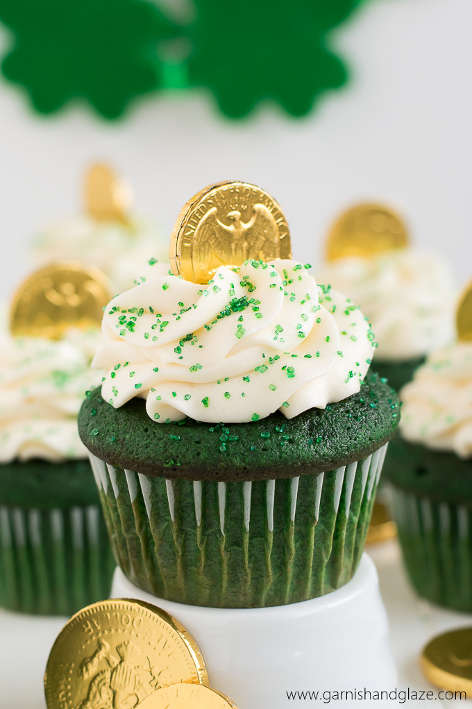a green cupcake with white icing and gold coins on top