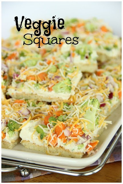 a stack of pizza squares topped with cream cheese sauce and chopped veggies