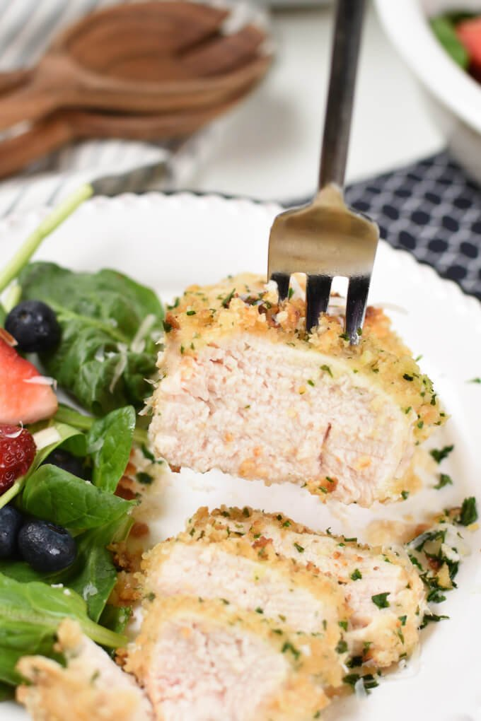 A bite of baked sliced chicken breast with a green salad