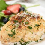a baked breaded chicken breast topped with grated parmesan cheese and chopped parsley
